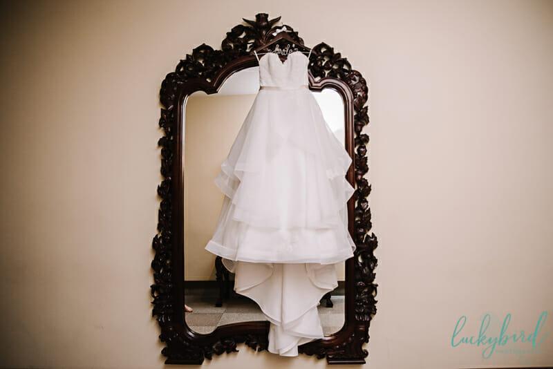 nazareth hall wooden mirror photo with dress hanging