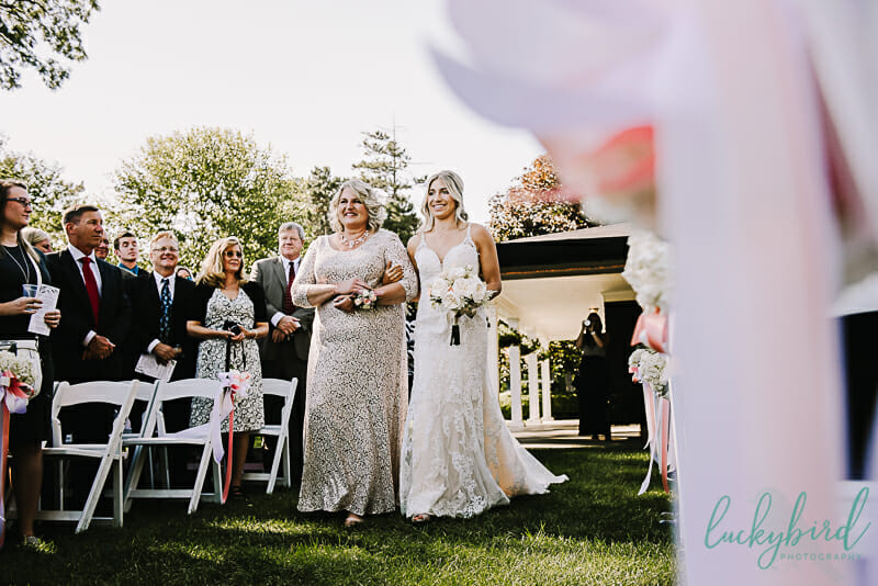 bride and her mom walking down the aisle at toledo country club