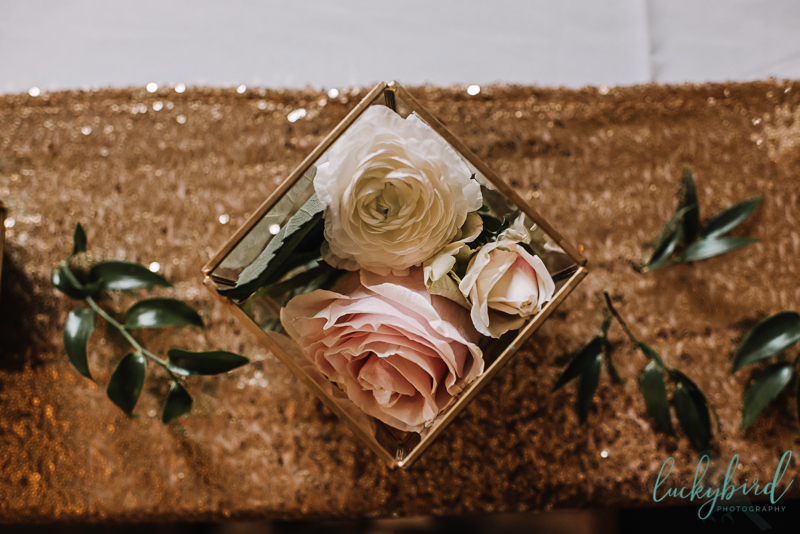ivory and blush roses on a gold sequined table runner