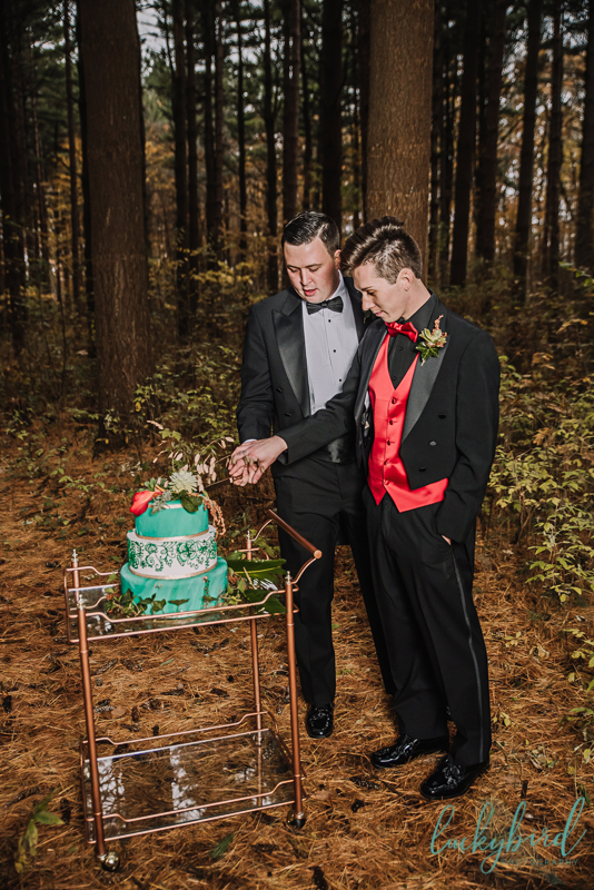 two grooms cutting a cake in toledo