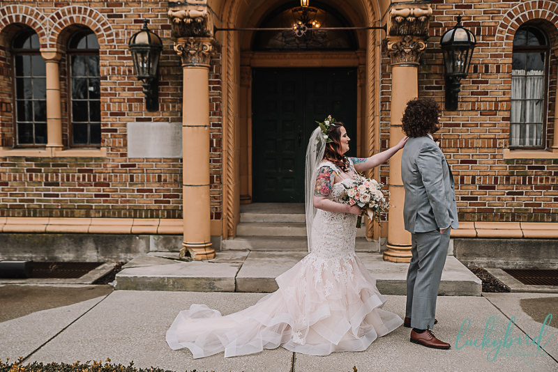 bride tapping groom in front of naareth hall for their first look
