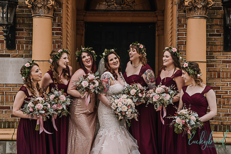 bridesmaids with floral crowns and burgundy in front of nazareth hall
