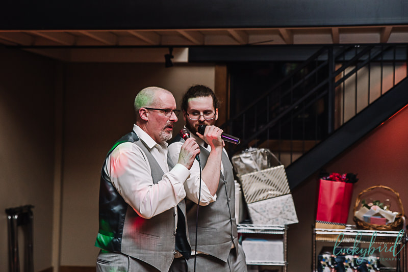 groom and dad singing karaoke inside nazareth hall's lady glen ballroom