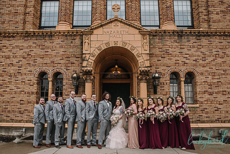 wedding party in front of nazareth hall with burgundy and gray