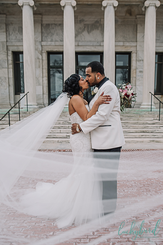 bride and groom kissing in front of marble steps at toledo museum