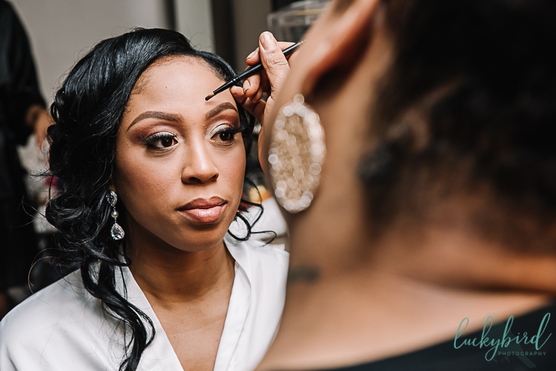 bride getting wedding makeup done at renaissance toledo