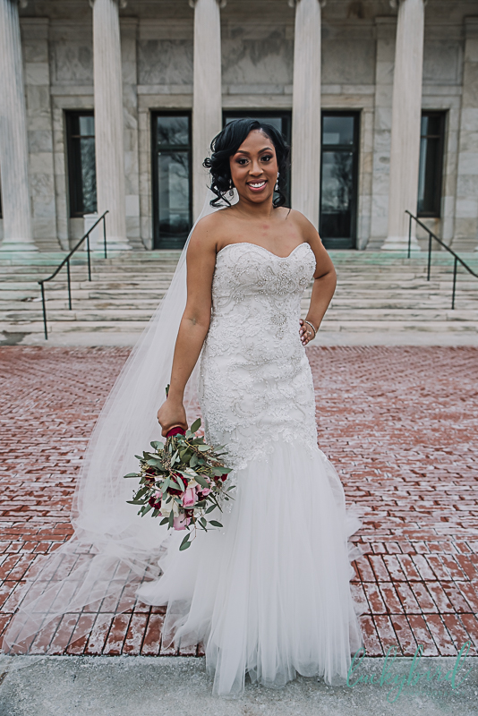 bride posing in front of marble steps at the toledo museum of art