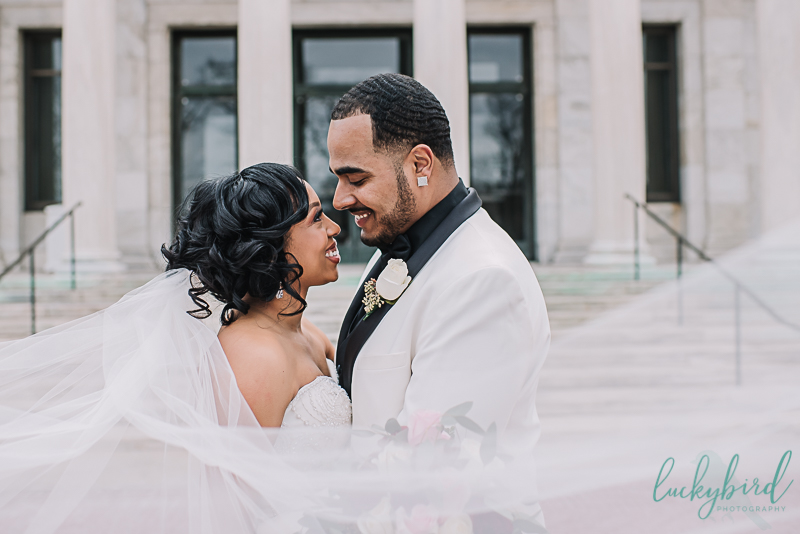 candid bride and groom in fromt of the toledo art museum