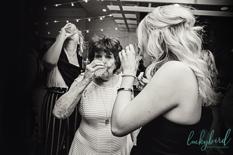 brides grandma taking a shot at a wedding