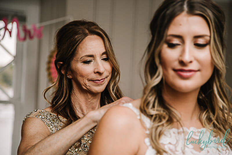mom helping bride get into belle amour dress