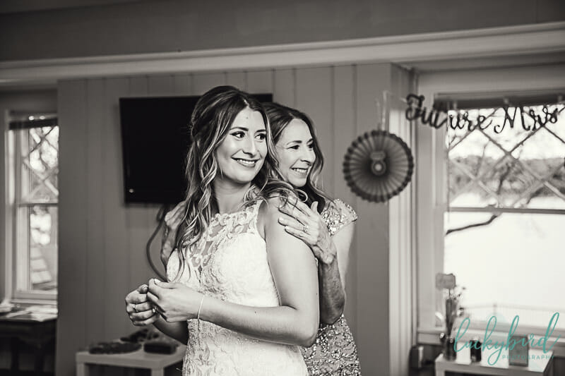 mother of the bride hugging bride after wedding dress
