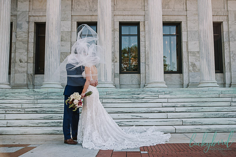 bride and groom under veil in the wind