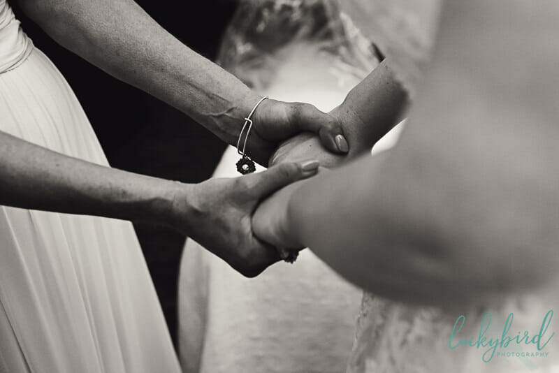 mom and bride holding hands