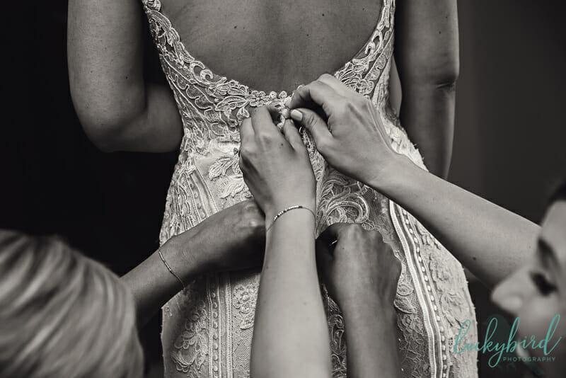 sisters helping bride in wedding dress