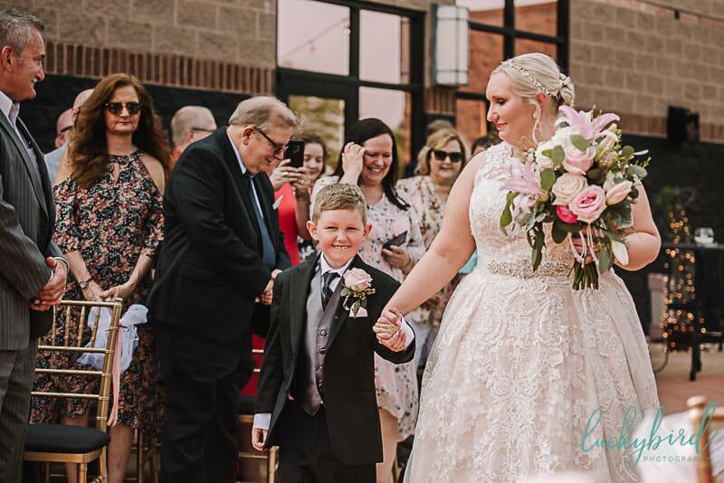 son walking bride down the aisle at the pinnacle