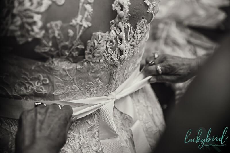 wedding dress with mom tying bow