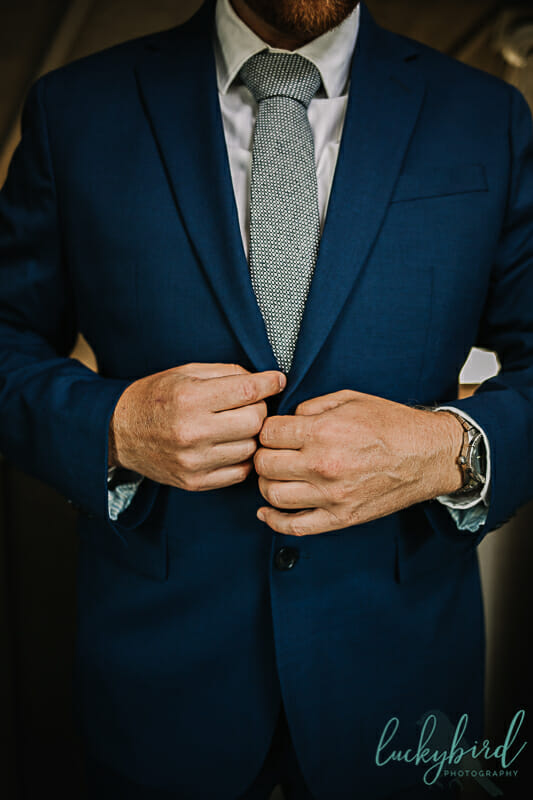 groom buttoning his suit at maumee bay wedding