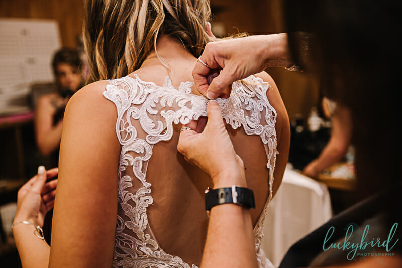 bride getting into her dress at the stables whitehouse