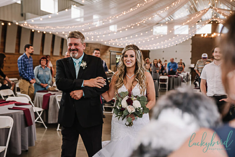 bride walking down the aisle at the stables whitehouse indoor ceremony
