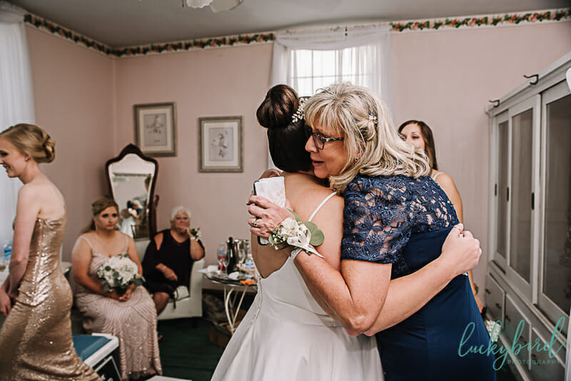 hugs with mom before wedding ceremony at nazareth hall