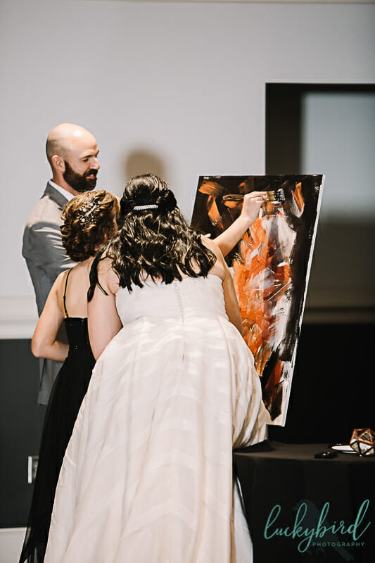 bride and groom and daughter unity ceremony at the zoo with paint