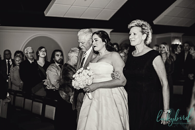 bride and her mom and dad walking down the aisle at malawi toledo zoo ceremony