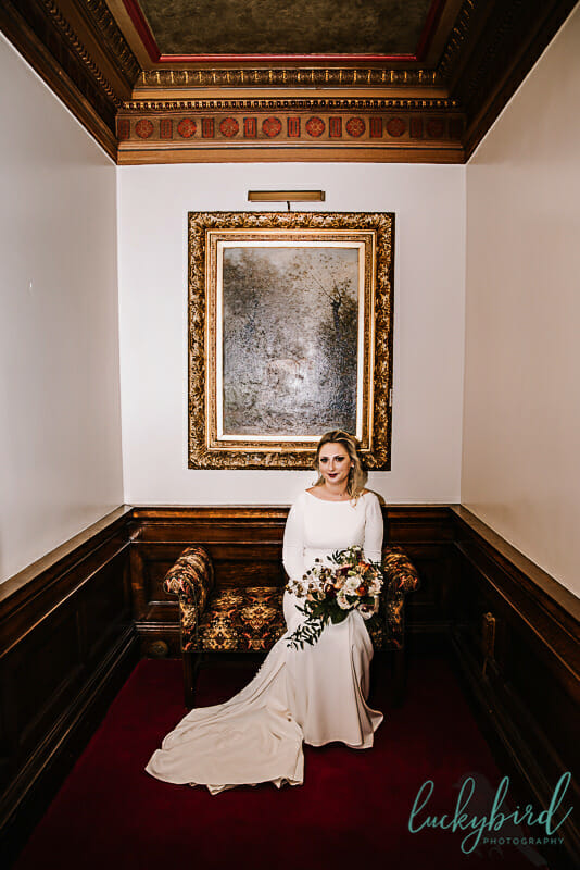 bride sitting on a bench before toledo club wedding