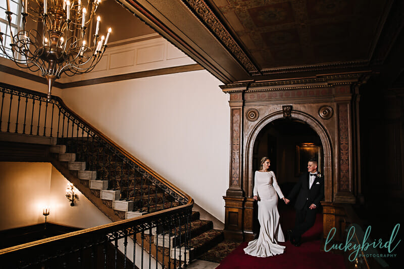 wedding photo of couple inside arch at toledo club wedding