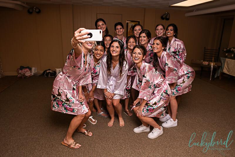 bridesmaids in robes at wedding taking selfie