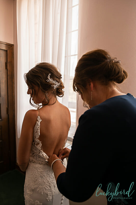 bride getting into her dress at nazareth hall