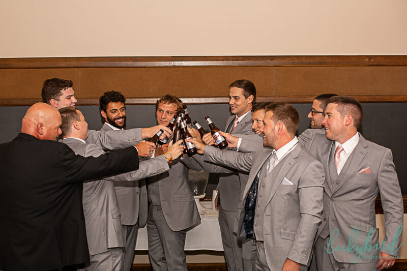 groomsmen toast with beers at nazareth hall