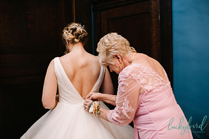 mom helping bride get into her dress
