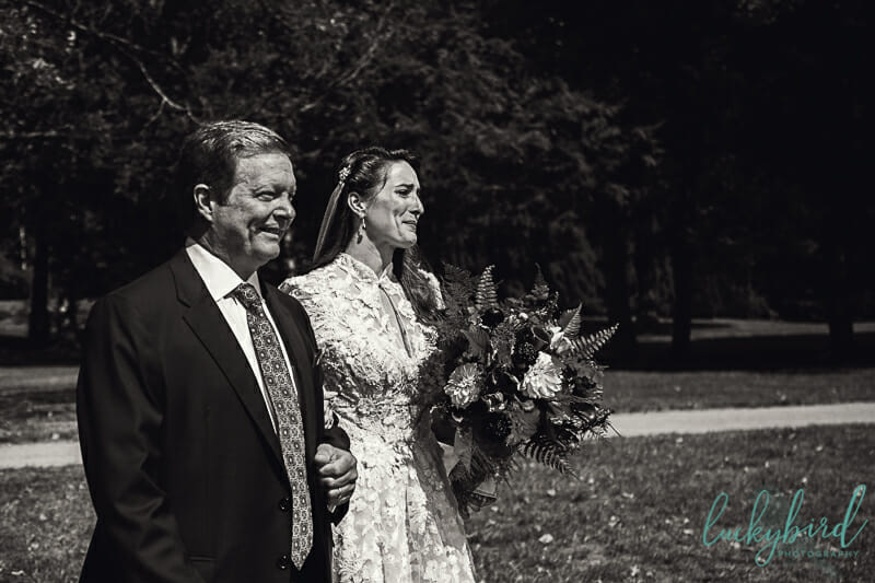 bride walking down the aisle crying with her dad