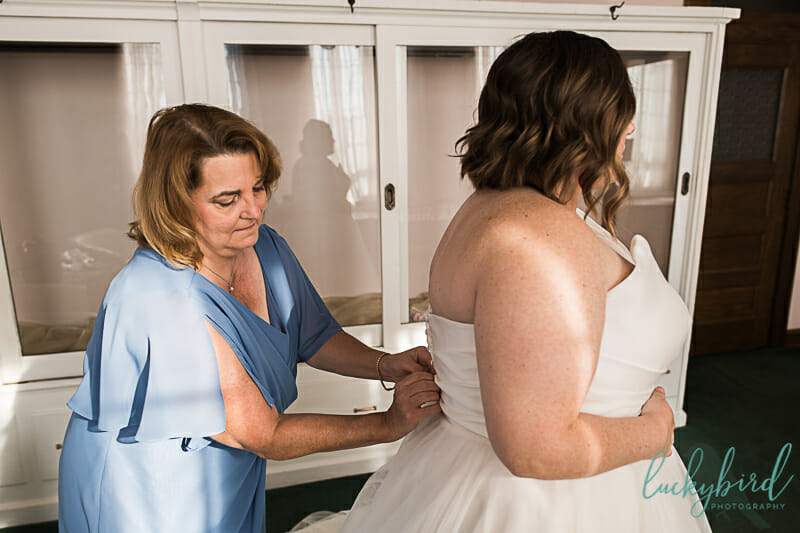 mom helping bride get into dress at nazareth hall