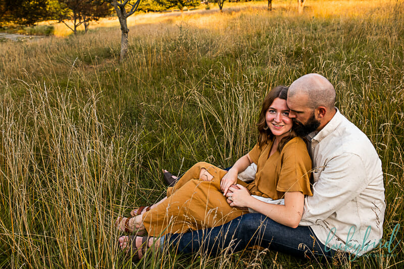 toledo botanical engagement photos sitting in a field
