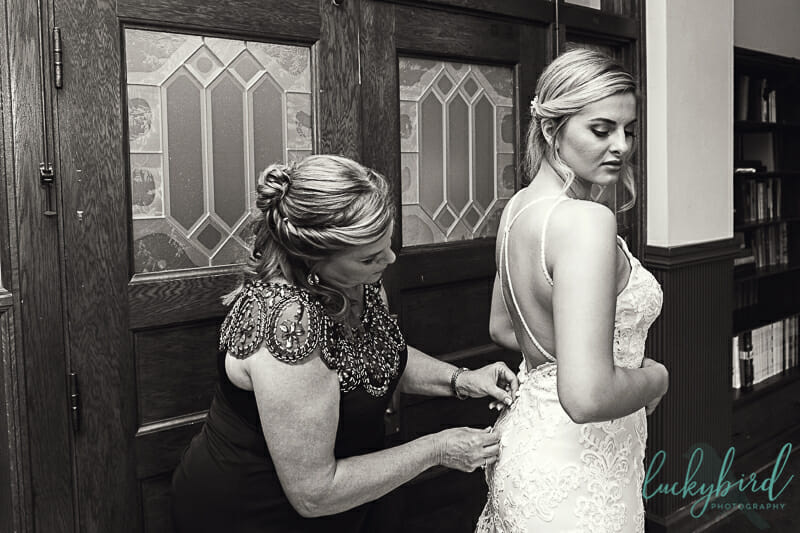 bride getting into wedding dress at nazareth hall riverview library