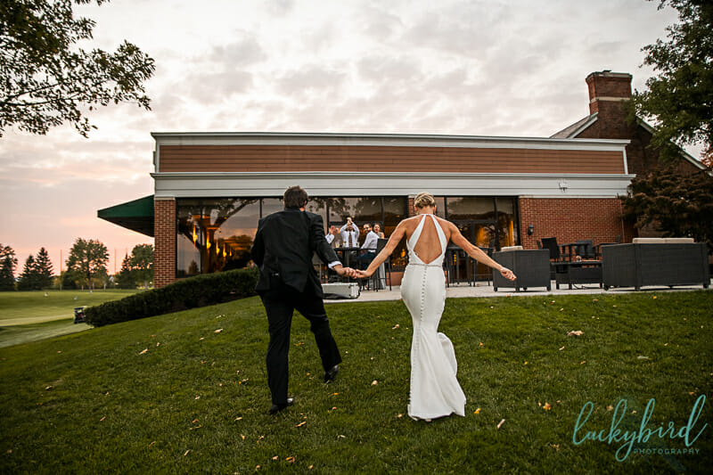 couple walking into inverness country club wedding reception