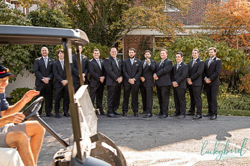 golf cart driving through groomsmen photo