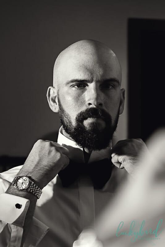 groom tying bow tie at renaissance toledo