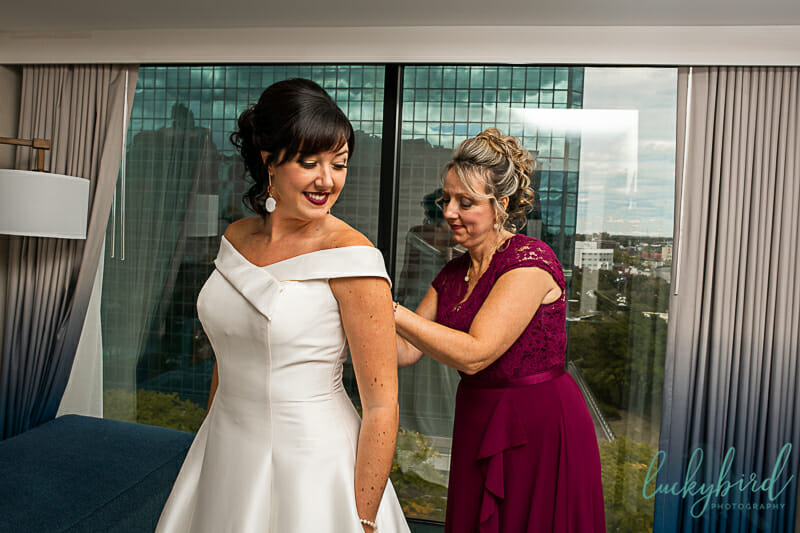 mom helping bride into her dress at renaissance toledo