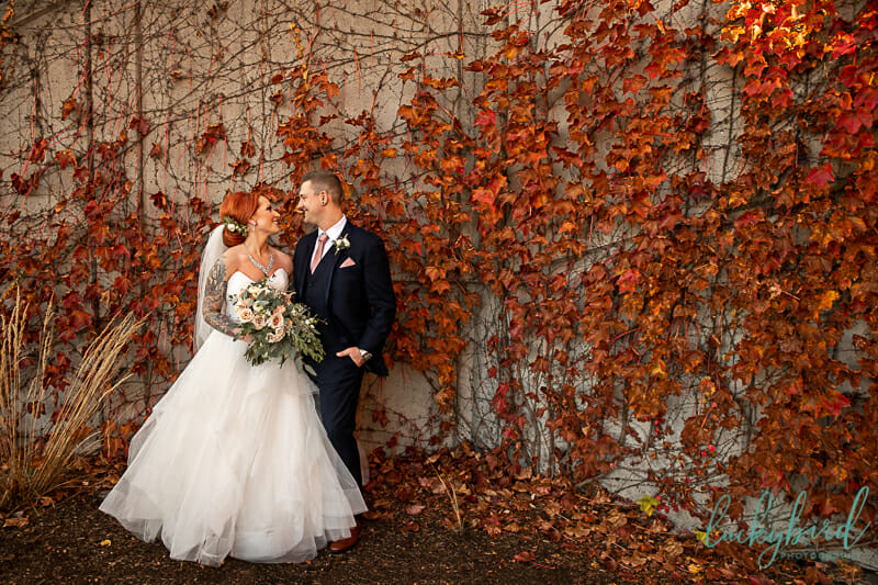 bride and groom in front of red leaves in downtown toledo fall wedding