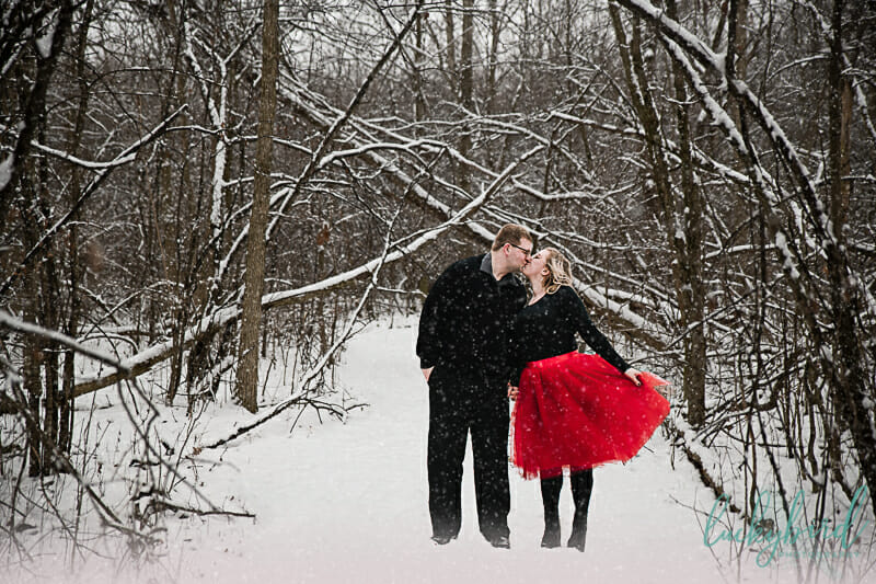 engagement session in the snow with red skirt