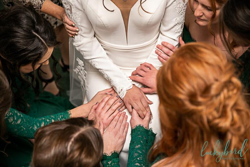 bridesmaids praying over bride at nazareth hall