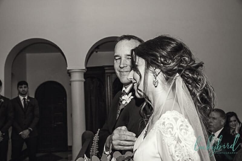 dad looking at bride walking down the aisle at the chapel at nazareth hall