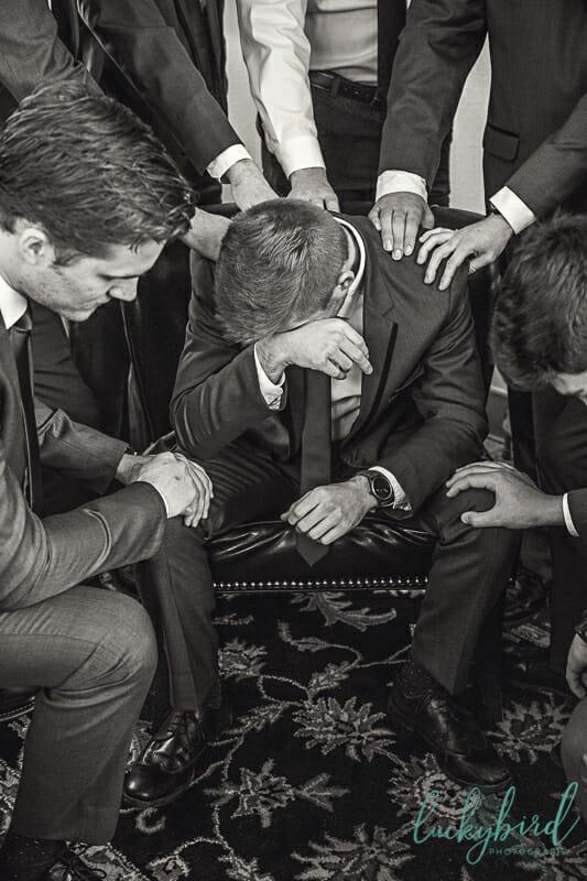 groom and groomsmen praying over groom at nazareth hall