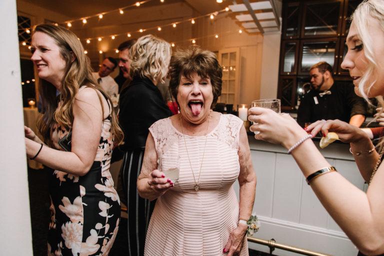 toledo country club wedding photo of grandma taking a shot at reception