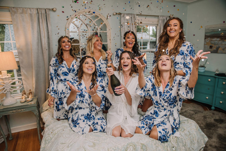 bridesmaids on bed tossing confetti with champagne