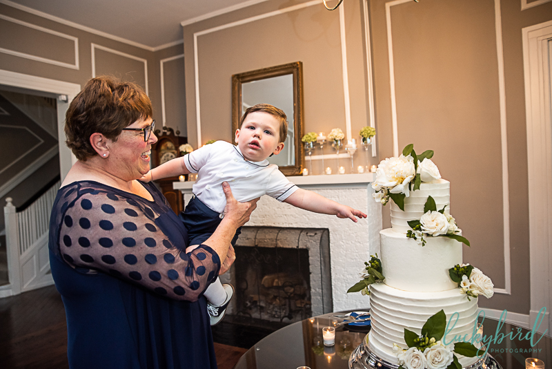 ring bearer touching wedding cake