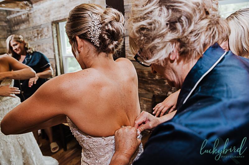 bride getting into dress for gideon owen wedding ceremony