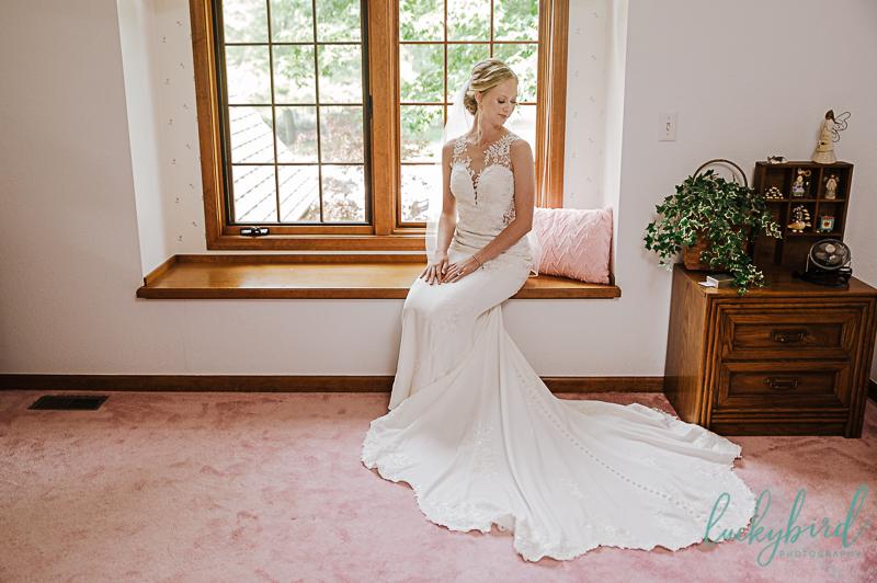 bride sitting in windo win childhood bedroom